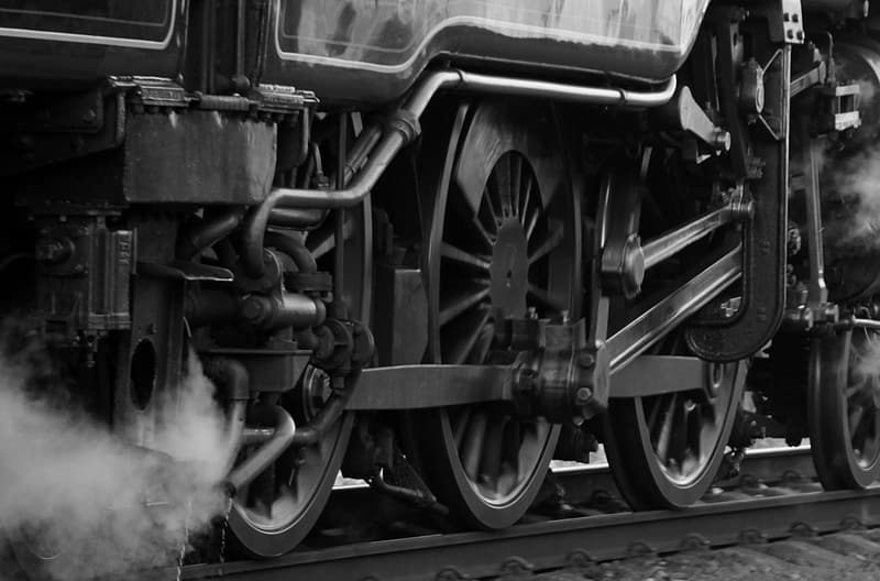 Grayscale photography of train wheels