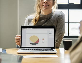 Woman in gray sweater using black tablet computer