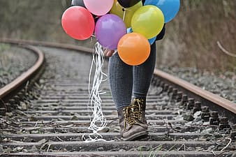 Selective focus photography of person walking on train rail while holding balloons