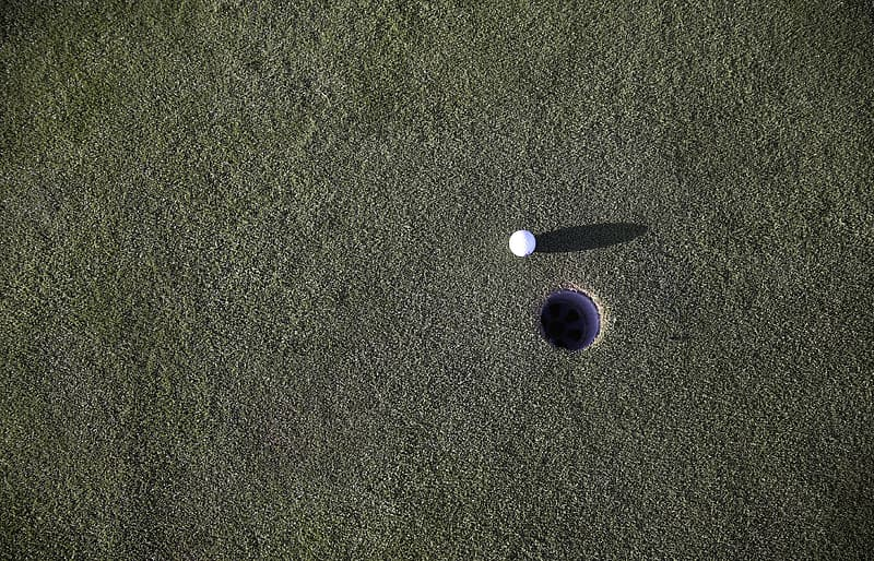 Golf ball and hole at daytime