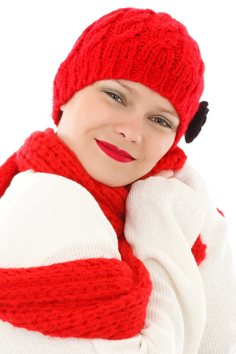 Woman in white knit long-sleeved shirt with red knit cap and scarf