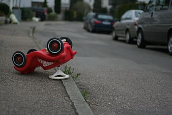 Red vehicle ride-on toy on road