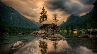 Green and brown tree painting, reflective photography of trees, rocks, and mountain with lightning strike in background