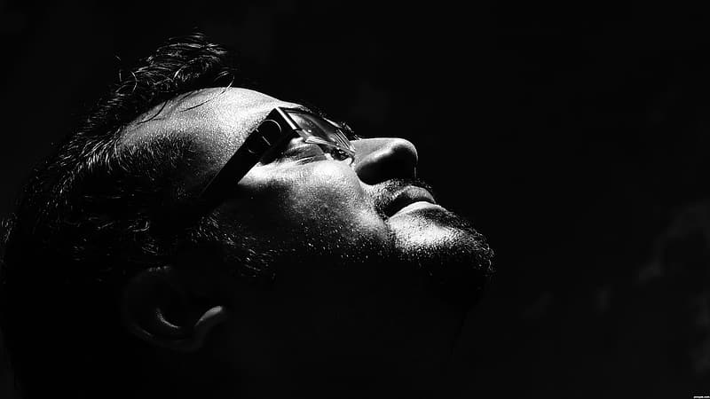 Grayscale photo of man wearing eyeglasses looking up
