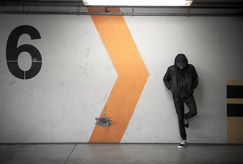 Man in black jacket and black pants standing beside white yellow and orange wall