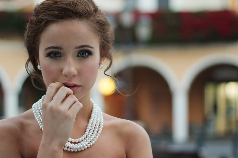 Selective photo of woman with right hand on lips wearing pearl necklace