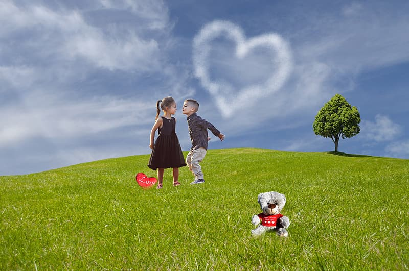 Boy and girl standing on grass elevated ground during daytime