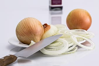 Sliced onions on saucer near knife