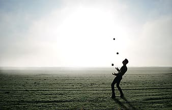 Man juggling on clear field