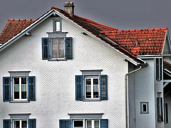 White and brown 3-storey house under dramatic sky