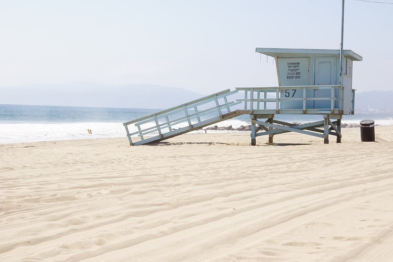 Lifeguard tower near body of water during daytime