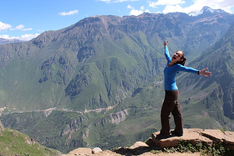 Woman in blue shirt and black pants on mountain during daytime