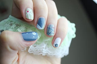 Woman showing blue, white, and green nail manicure