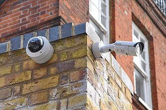 Two white assorted-type wall mounted security cameras on brown brick wall