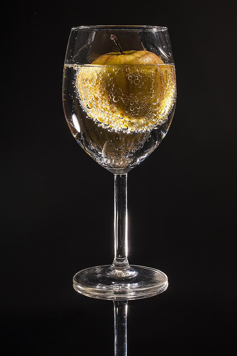 Clear wine glass with liquid and brown apple