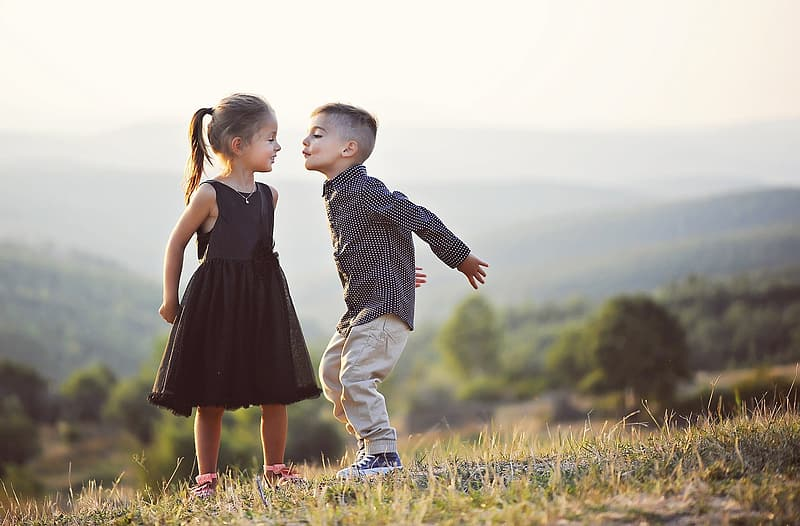 Boy about to kiss girl on lawn field