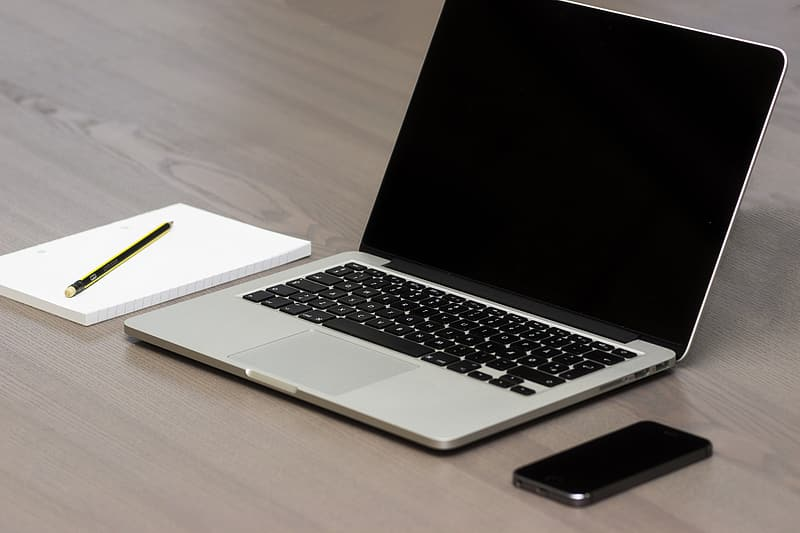 MacBook Pro beside white notebook and gold fountain pen