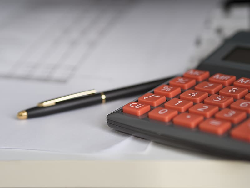 Black and brown pen near gray and red desktop calculator
