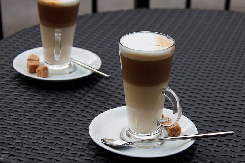 Clear glass mug filled with cappuccino with white ceramic saucer and stainless steel spoon on brown wicker table top