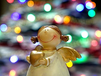 Angel holding heart figurine with bokeh light