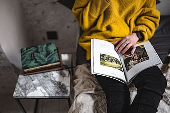 Person in yellow jacket holding book