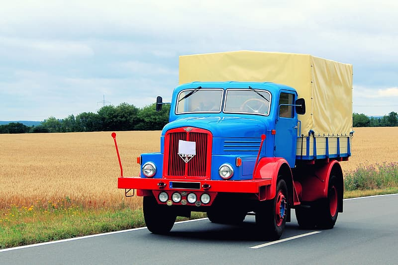 Blue, red, and beige truck on road near grass field during daytime