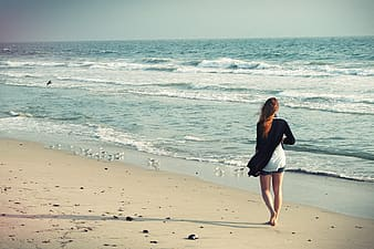 Woman walking beside of beach during daytime