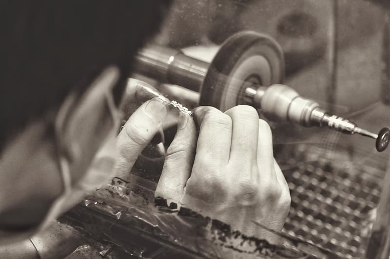 Grayscale photography of man cleaning jewelry with bench grinder