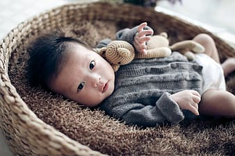 Baby in gray button up shirt lying on brown textile