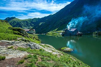 House near calm lake surrounded by mountain