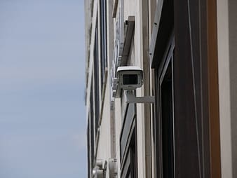 White security camera mounted on white wall