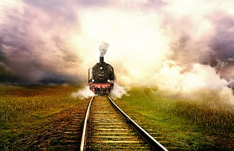 Steam engine train travelling on  track under white clouds