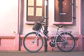 Bicycle parked beside post
