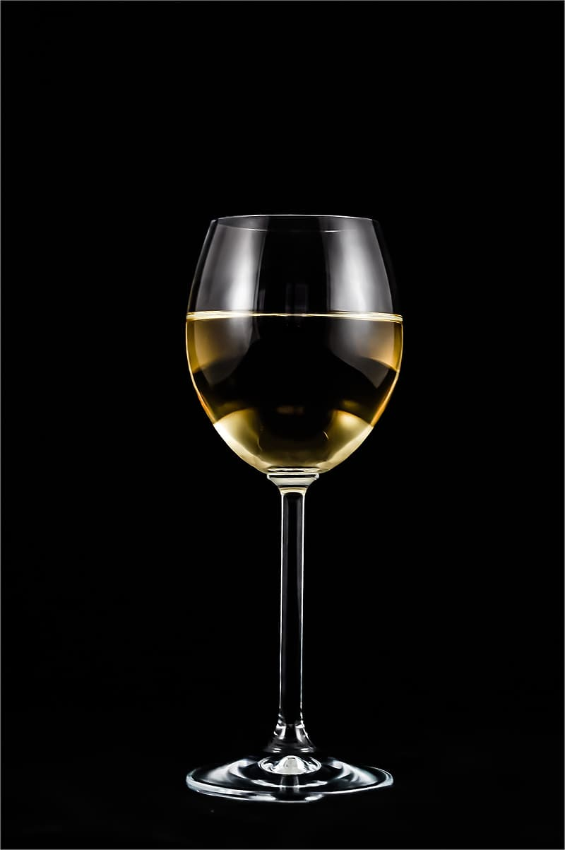 Photograph of glass of white on black background