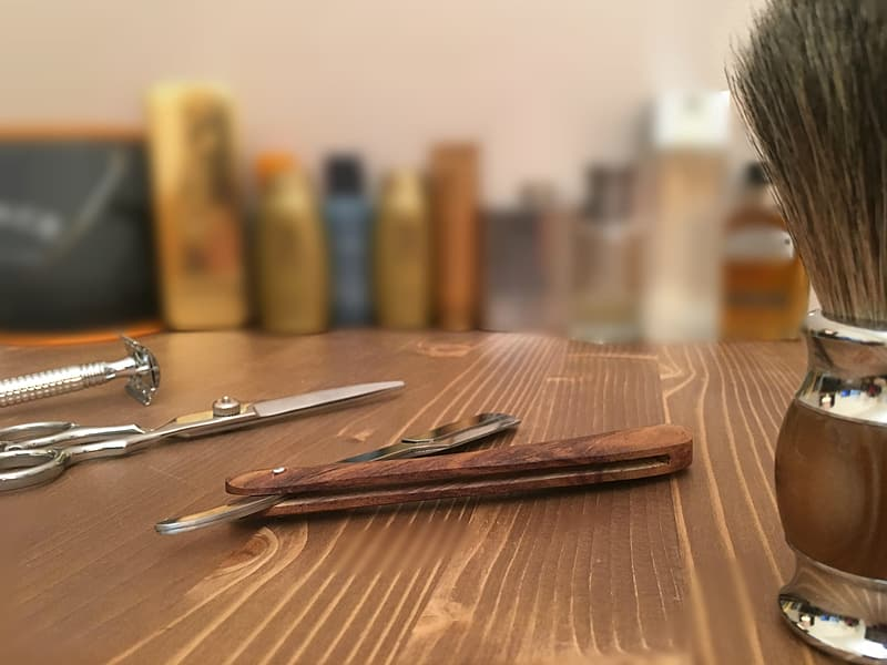 Silver nail cutter on brown wooden table