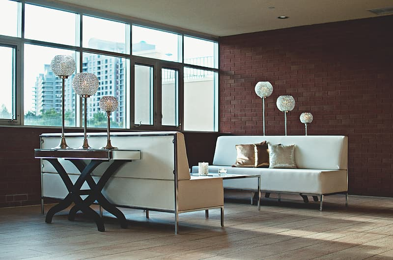 Two white leather sofa on brown wooden parquet floor inside room