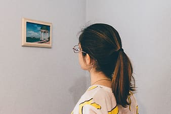 Woman looking at picture on wall
