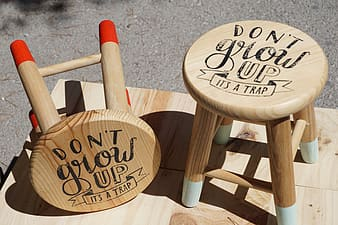 Two round beige don't grow up-printed wooden stools on beige wooden board