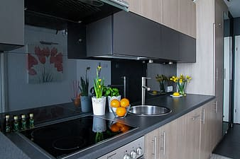 Black marble-top kitchen table with gray wooden base cabinets