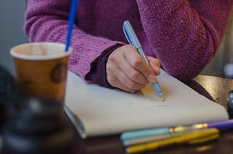 Selective focus photography of person holding pen writing on paper on table near coffee cup