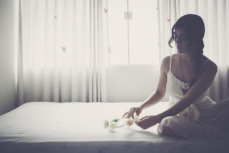 Woman in white tank top and white pants sitting on bed