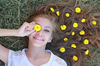 Woman holding yellow mums flower in her eye