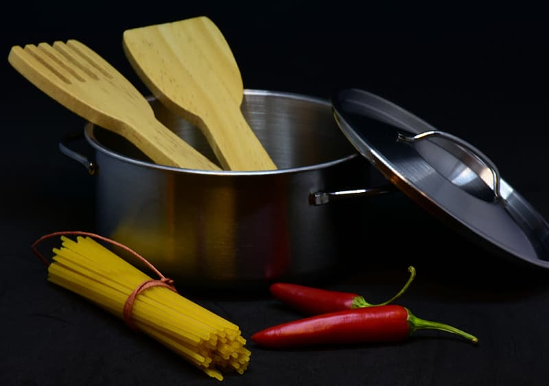 Stainless steel spoon and fork on stainless steel cooking pot