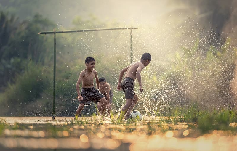 Tilt-shift photography of children playing with water