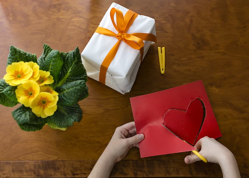 Person cutting red construction paper near gift box