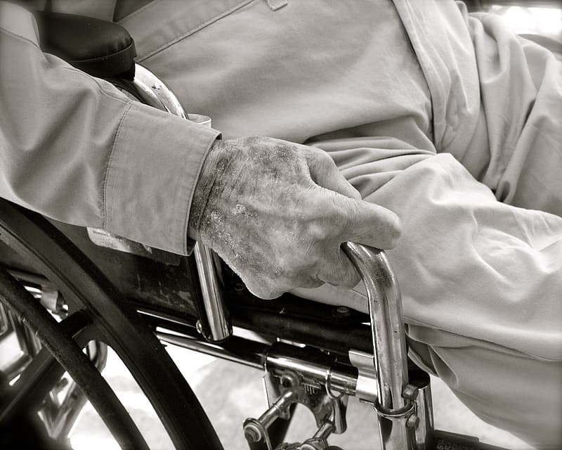 Grayscale photo of person seating on wheelchair