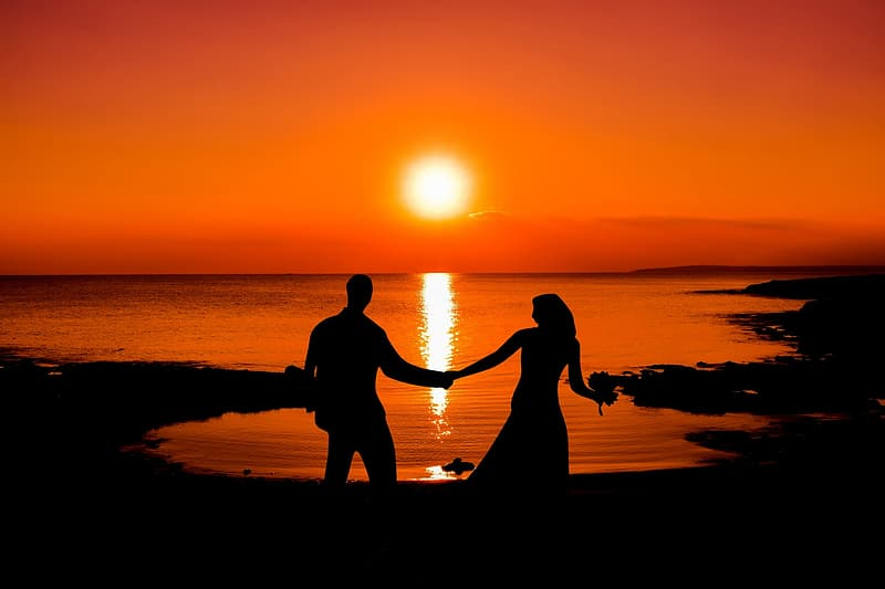 Silhouette of man and woman holding hand stands near ocean at sunset