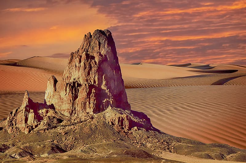 Brown rock formation on brown sand during sunset
