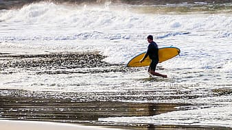 Person holding yellow surfboard while walking on seashore