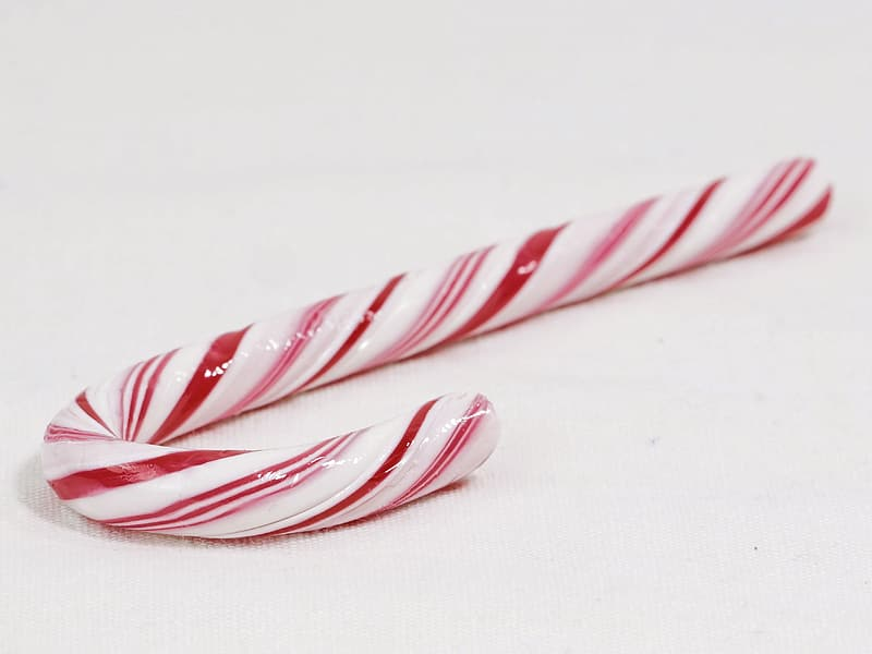 Red and white candy cane on white surface